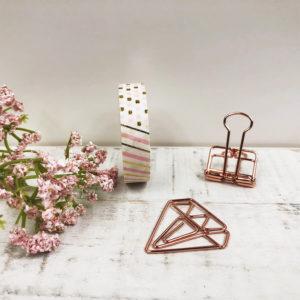 Washi Tape mit einem Muster aus rosanen und goldenen Elementen. Das Bild ist dekoriert mit rosé goldenen Clips und einer Blume.