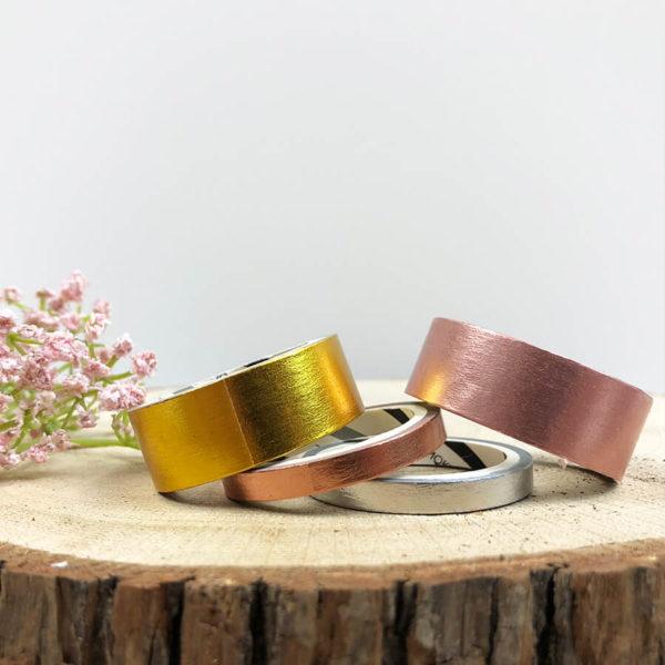 Washi Tape Set, bestehend aus einem goldenen, rosé goldenen, silbernen und rosanem Washi Tape von vorne auf einem Holzbrett.