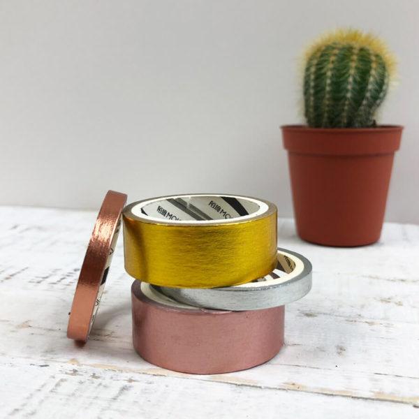 Washi Tape Set, bestehend aus einem goldenen, rosé goldenen, silbernen und rosanem Washi Tape von vorne vor einem Kaktus fotografiert.