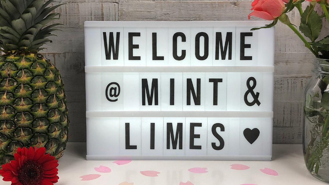 """Light Box mit der Aufschrift """"Welcome Mint & Limes"""" mit Konfetti, einer Ananas und Roten Rosen."""