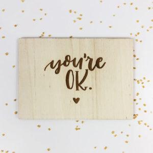 """Holzpostkarte mit Aufschrift """"You're OK"""" und kleinem Herz. Von oben fotografiert."""