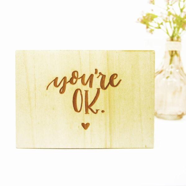 """Holzpostkarte mit Aufschrift """"You're OK"""" und kleinem Herz neben einer Vase mit einer Blume."""